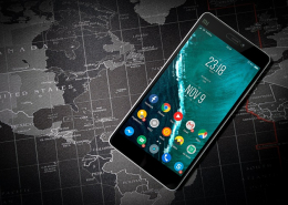 Smartphone with Android-Icons on the start screen in front of a world map
